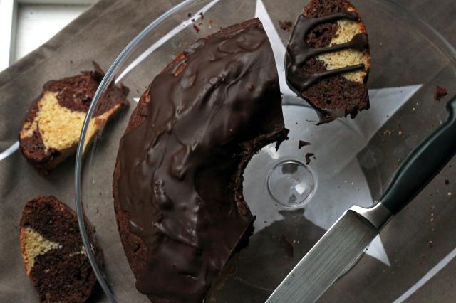Marmorkuchen und -stücke mit Glasur auf einer Glasplatte mit Messer